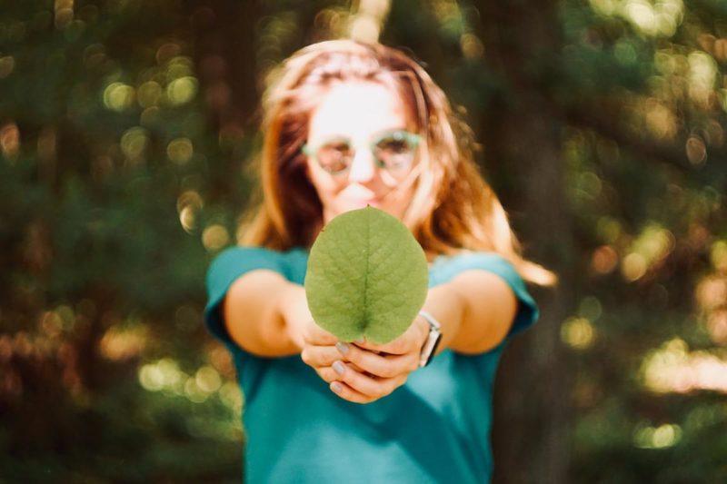 Jonge vrouw met groen boomblad in haar hand.